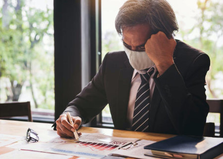 Man wearing a mask while looking at documents.