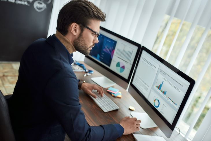 Working at a desktop with two computer screens.